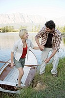 Couple at lake stepping out of rowing boat, man helping woman