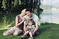 Young Family with boy 4_7 sitting in front of lake, posing
