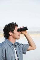 Man standing outdoors using binoculars