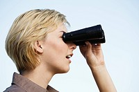 Woman standing outdoors using binoculars, close_up