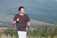 Young man outdoors, hiking with Nordic_walking sticks