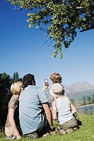 Young Family sitting on grass looking at compass pointing at mountains, outdoors