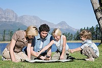 Young Family sitting on grass looking at map, outdoors