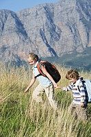 Two children outdoors, hiking with backpack, mountains in background