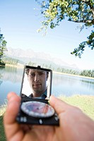 Young man holding compass, outdoors, face reflected in compass mirror