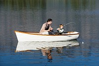 Father and son 4_7 sitting in rowing boat on lake, fishing with fishing rod