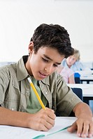 School boy10_13 writing in classroom, concentrating