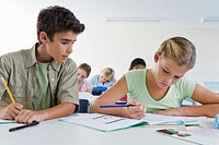 Boy and girl 10-13 in classroom, boy copying girls work, cheating (thumbnail)
