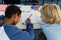 Two boys 10_13 in classroom working together over exercise, team work