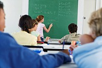 Group of school children 10_13 in classroom looking at blackboard
