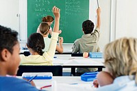 Group of school children 10_13 in classroom with hands raised