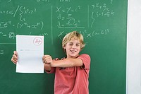 Boy 10-13 holding up test paper with A+ mark on it, in front of blackboard (thumbnail)