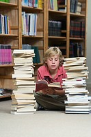 Boy 10_13 in library, reading and sitting between two piles of school books