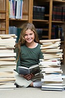 Girl 10_13 in library, reading and sitting between two piles of school books