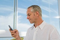 Mature man at window using cell phone, looking at display
