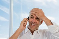 Mature man at window smiling, using cell phone, holding hand to head (thumbnail)