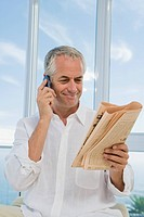 Mature man smiling, using Cell phone and reading financial newspaper