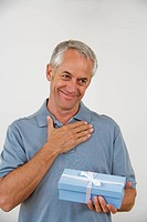 Senior man holding blue present in hand