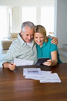 Mature couple happy and hugging, looking at finance statement