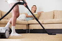 Senior couple, man vacuuming at home, woman lying on sofa watching