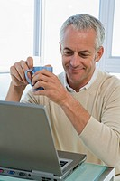 Mature man working with Laptop computer, holding coffee cup