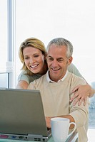 Mature couple working with Laptop computer, smiling