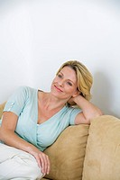 Mature woman sitting on sofa, smiling, portrait