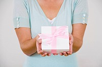 Senior woman holding pink present, detail of hands