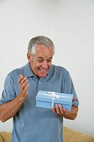 Senior man with excited expression, holding blue present in hand