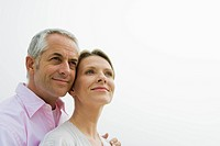 Mature couple looking into distance, smiling