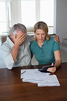 Mature couple stressed, looking at finance statement