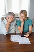 Mature couple worried, looking at finance statement