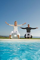 Mature couple sitting at poolside on Gymnastic balls doing Pilates exercises