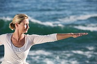 Mature woman with arms outstretched, with waves breaking in background