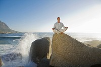Mature man sitting doing yoga on top of rock outcrop with waves in background