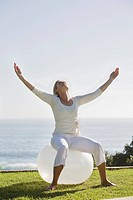Mature woman with arms outstretched sitting on exercise ball in garden