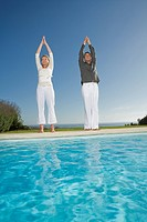 Mature couple standing at poolside outdoors doing yoga exercises