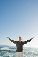 Mature man with arms outstretched, smiling with ocean in background