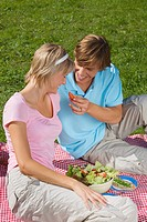 Young couple sitting on Picnic blanket sharing Salad