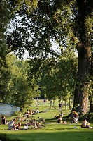 Sunbathers on edge of Eisbach river in English Garden Munich Germany