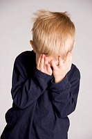 A young child hides his face in his hands