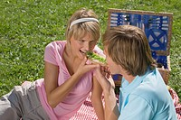 Young couple having picnic and eating sandwich, close_up