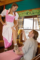 Young woman standing on table at Oktoberfest, Munich, Germany