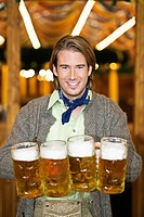 Waiter holding 4 Mass beer jugs at Oktoberfest, Munich, Germany (thumbnail)