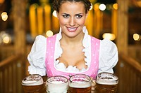 Waitress holding 4 Mass beer jugs at Oktoberfest, Munich, Germany