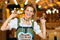 Young woman holding up her pigtails at Oktoberfest, Munich, Germany