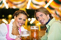 Close_up of young couple drinking beer at Oktoberfest, Munich, Germany