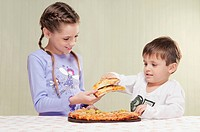 Girl and her brother holding slices of pizza