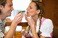 Close_up of young couple having snack at Oktoberfest, Munich, Germany