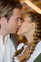 Close_up of young couple kissing at Oktoberfest beer festival, Munich, Germany